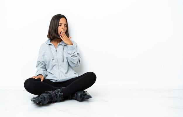 Młoda azjatykcia kobieta z wrotkami na podłodze ziewanie i obejmowanie ręką szeroko otwarte usta