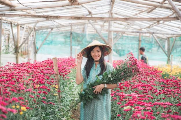 Młoda azjatykcia kobieta zbiera rumianków kwiaty