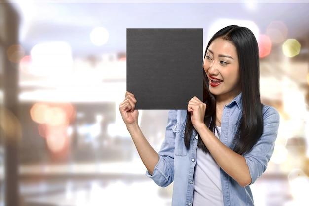 Młoda azjatykcia kobiety mienia znaka deska z pustą przestrzenią
