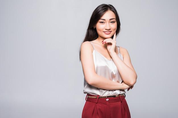 Młoda azjatykcia kobiety pozycja odizolowywająca na biel ścianie