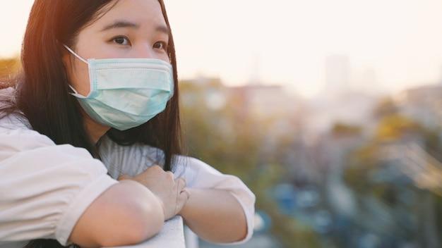 Młoda azjatykcia millennial gen z kobiety pozycja przy dachu uczuciem nudzi i patrzeje pejzaż miejskiego podczas gdy będący ubranym maskę