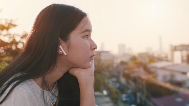 Młoda azjatykcia millennial gen z kobiety pozycja przy dachu uczuciem nudzi i patrzeje pejzaż miejskiego podczas gdy słuchający muzyka