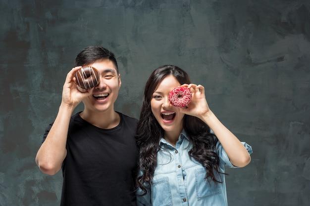 Młoda azjatykcia para cieszy się jedzenie słodki kolorowy pączek