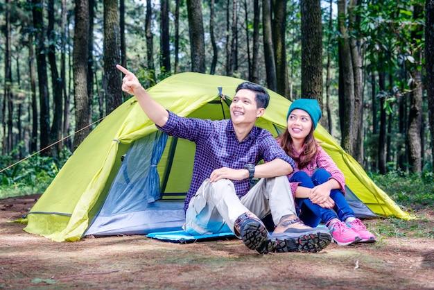 Młoda azjatykcia para siedzi przed namiotem i patrzeje widok wokoło