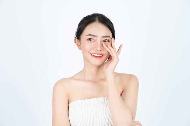Młoda azjatykcia piękna dziewczyna w białym podkoszulku, ma zdrową i jasną skórę.