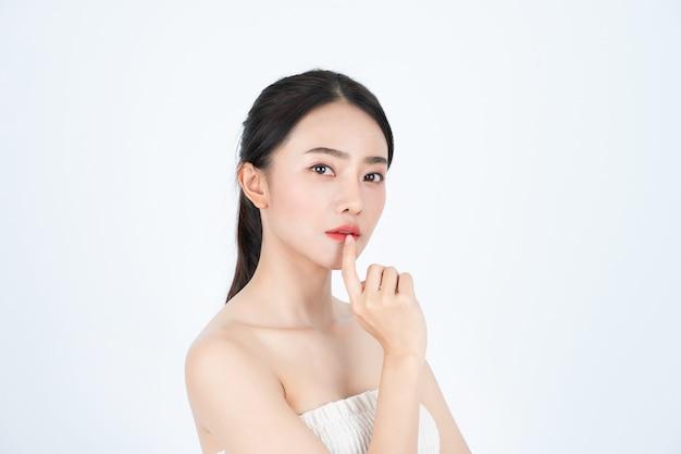 Młoda azjatykcia piękna kobieta w białym podkoszulku, ma zdrową i jasną skórę.
