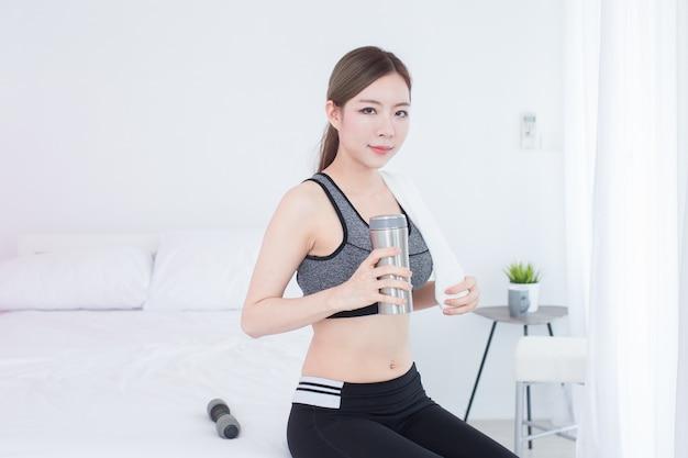 Młoda azjatykcia piękna sprawności fizycznej dziewczyna pije butelkę woda po treningu