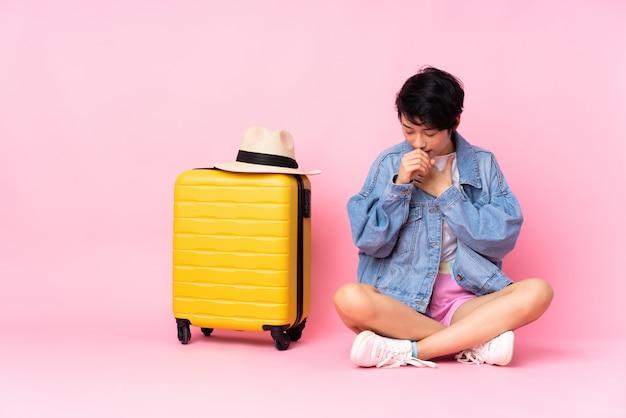 Młoda azjatykcia podróży kobieta nad obsiadaniem na podłoga