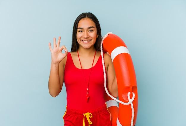 Młoda azjatykcia ratownik kobieta odizolowywał rozochoconego i ufnego pokazuje ok gest.