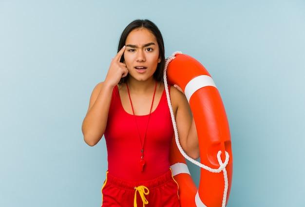 Młoda azjatykcia ratownik kobieta pokazuje rozczarowanie gest z palcem wskazującym.