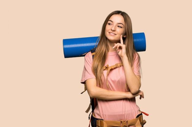 Młoda backpacker kobieta myśleć pomysł podczas gdy przyglądający up na kolor żółty ścianie