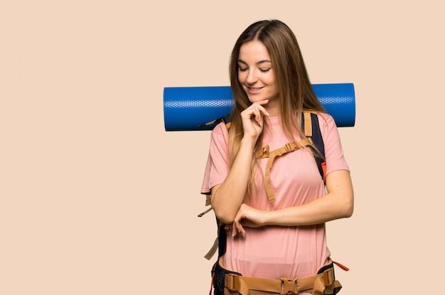 Młoda backpacker kobieta patrzeje w dół z ręką na podbródku na kolor żółty ścianie