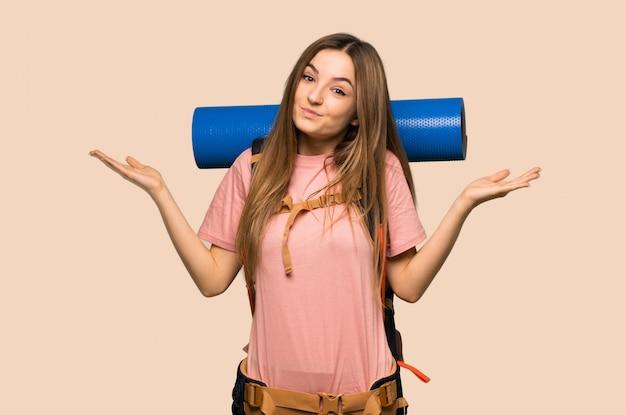 Młoda backpacker kobieta robi nieistotnemu gestowi podczas gdy podnoszący ramiona na kolor żółty ścianie
