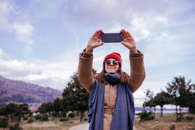 Młoda backpacker kobieta wycieczkuje w naturze. pochmurny zimowy dzień. robienie zdjęć przy użyciu telefonu komórkowego