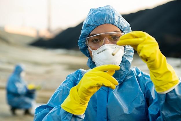Młoda badaczka w ochronnej odzieży roboczej trzyma próbkę toksycznej gleby w kolbie przed twarzą podczas dochodzenia ekologicznego z kolegą