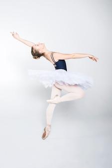 Młoda balerina ćwiczy ruchy baletowe