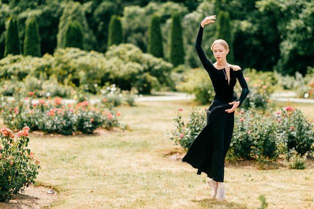 Młoda balerina w czerni sukni pozuje balet pozy i pokazuje w lato parku
