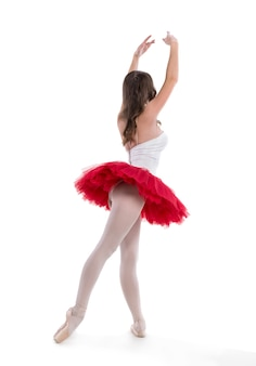 Młoda baletnica pozuje i tańczy na białym tle w studio