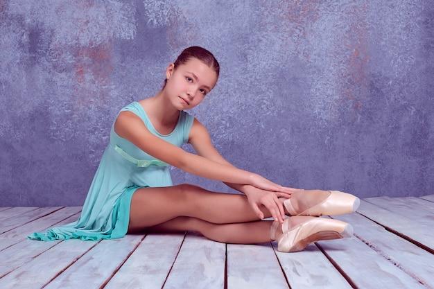 Młoda baletnica siedzi na drewnianej podłodze na liliowym tle