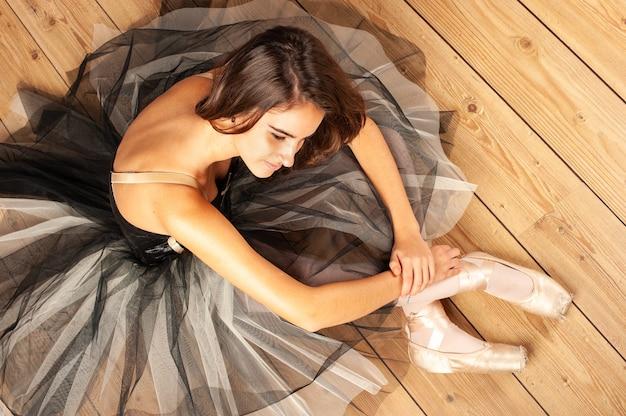 Młoda baletnica siedzi na drewnianej podłodze