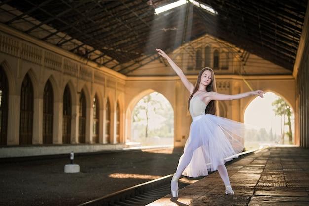 Młoda baletnica w białej długiej spódnicy stoi w wdzięcznej pozie na pointes