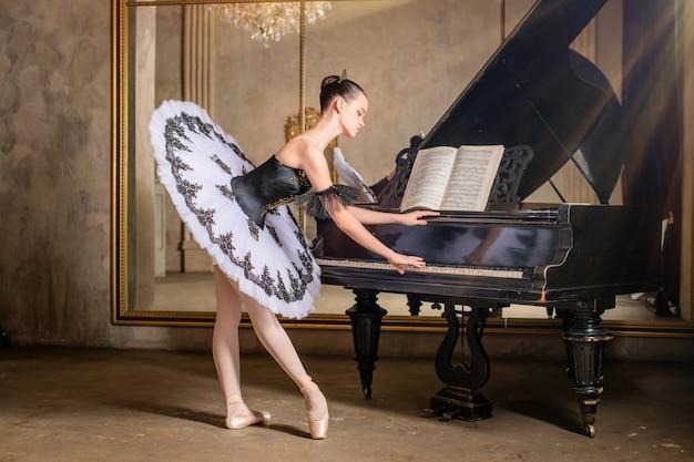 Młoda baletnica w białej spódniczce tutu gra na pięknym starym pianinie