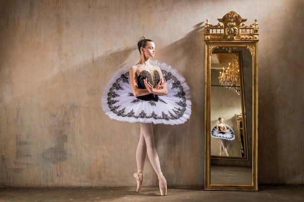 Młoda baletnica w białej spódniczce tutu pozuje obok pięknego starego mummera w klasycznym wnętrzu, wielokrotnie odbijając się