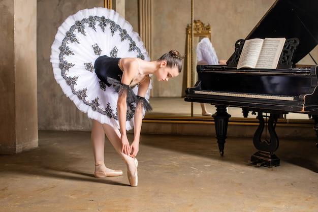 Młoda baletnica w białej spódniczce tutu tańczy na pięknym starym pianinie w zabytkowym wnętrzu