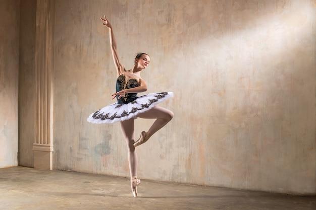 Młoda baletnica w białej spódniczce tutu tańczy w świetle reflektorów w scenie vintage