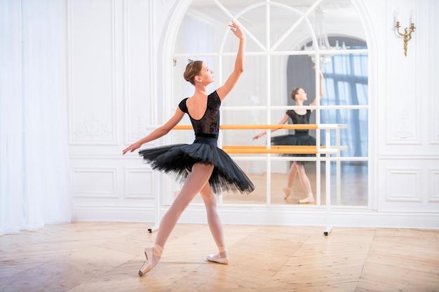Młoda baletnica w czarnej spódniczce tutu stoi w wdzięcznej pozie na pointe w dużej jasnej sali przed lustrem.