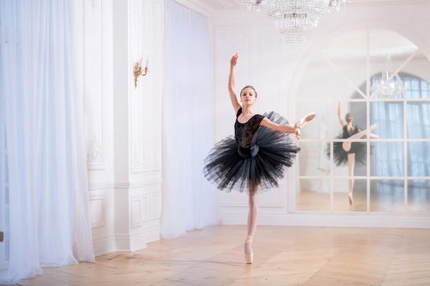Młoda baletnica w czarnej spódniczce tutu tańczy na pointe w dużej jasnej sali przed lustrem.