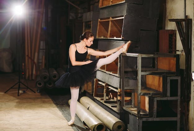 Młoda baletnica w czarnej sukience trenuje za kulisami.