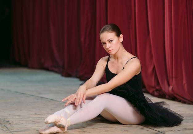Młoda baletnica w czarnej sukni trenuje za kulisami.