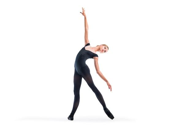 Młoda baletnica w czarnych pointe butach i trykotach pozuje w pełnej wdzięku pozie, izolowana na białym tle