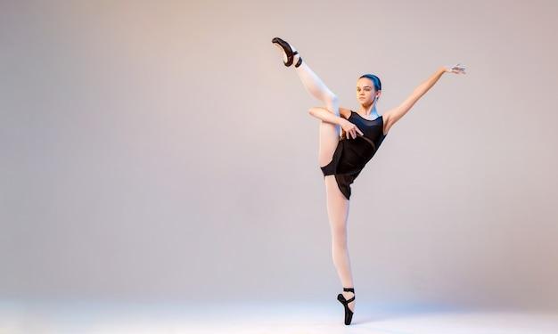 Młoda baletnica w czarnym stroju kąpielowym i pointes tańczy na jasnym tle.