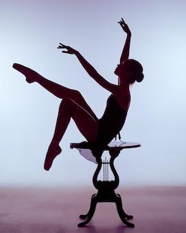 Młoda baletnica w niebieskiej sukience siedzi na drewnianym krześle na liliowym tle. balerina ma na sobie pointe buty. strzelanie konturowe - sylwetka dziewczyny