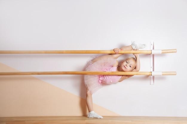 Młoda baletnica w różowej sukience jest zaangażowana w studio baletowe