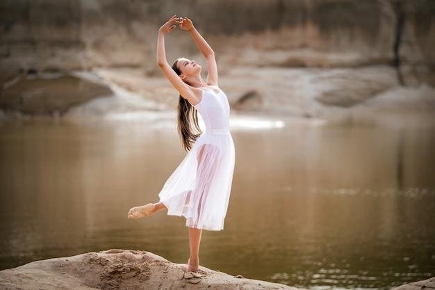 Młoda baletnica w zgrabnej pozie stoi na skraju piaszczystego klifu