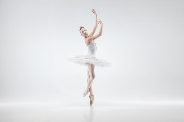 Młoda baletnica wdzięku na tle białego studia