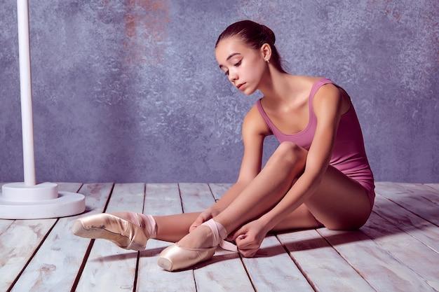 Młoda baletnica zakłada baletki na drewnianej podłodze na różowym tle
