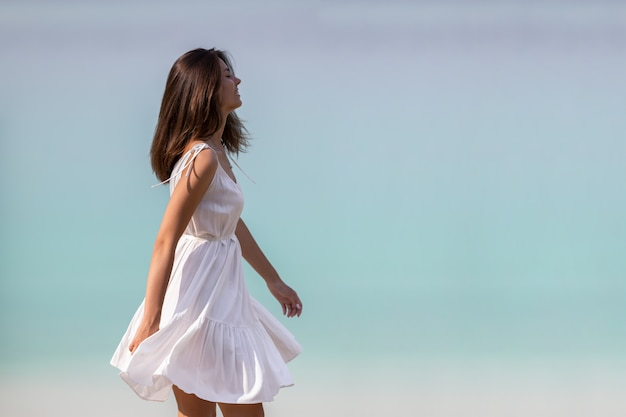 Młoda, bardzo piękna dziewczyna z długimi włosami w białej sukni nad jeziorem. dziewczyna wiruje, tańczy ze szczęścia i cieszy się resztą.