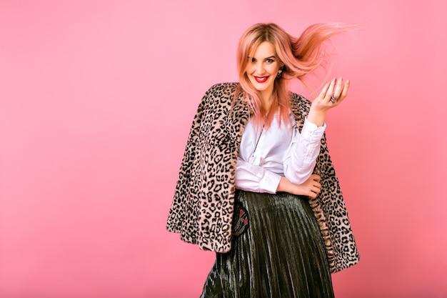 Młoda, bardzo seksowna, wspaniała kobieta bawi się włosami, ubrana w wieczorowy musujący strój koktajlowy i modny płaszcz z nadrukiem futra lamparta, różowe tło, pozytywne emocje.