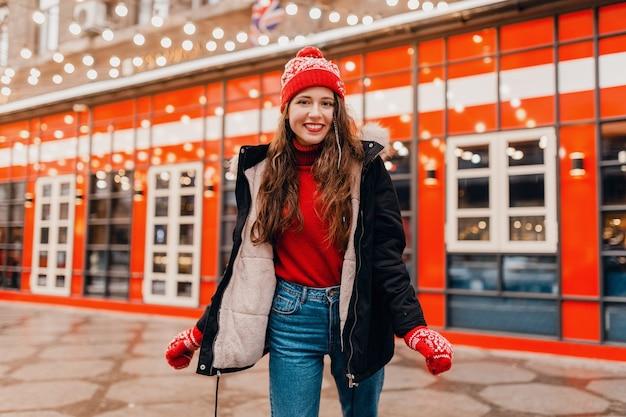 Młoda, bardzo uśmiechnięta, podekscytowana szczęśliwa kobieta w czerwonych rękawiczkach i czapce na sobie zimowy płaszcz spacerujący po mieście świąteczna ulica, trend w modzie w stylu ciepłych ubrań