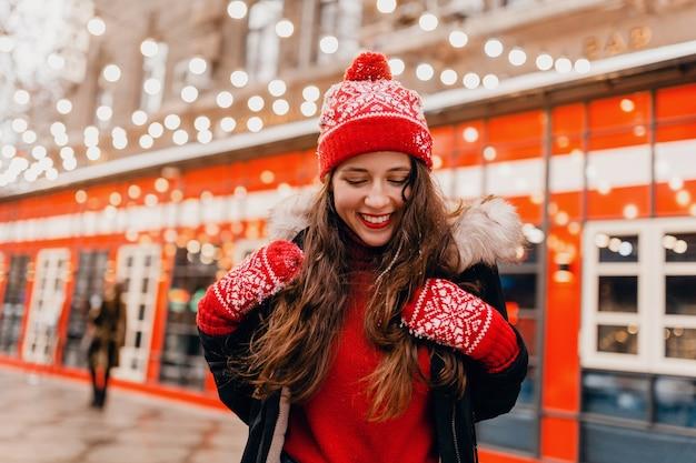 Młoda, bardzo uśmiechnięta szczęśliwa kobieta w czerwonych rękawiczkach i czapce z zimowym płaszczem spacerującym po mieście świąteczna ulica, trend w modzie w stylu ciepłych ubrań