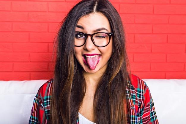 Młoda, bardzo uwodzicielska hipsterka bawi się i pokazuje długi język i mrugnęła, ubrana w kraciastą koszulę i jasne okulary, długie włosy i jasny makijaż. czerwony mur miejski.
