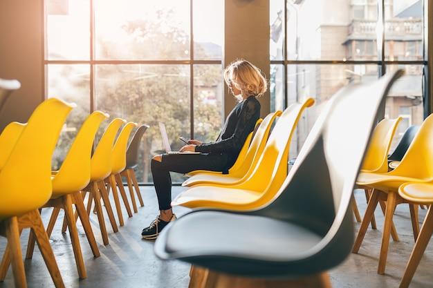 Młoda bardzo zajęta kobieta siedzi samotnie w sali konferencyjnej