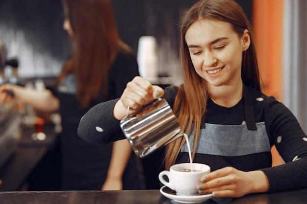 Młoda barista dziewczyna robi kawę i uśmiecha się