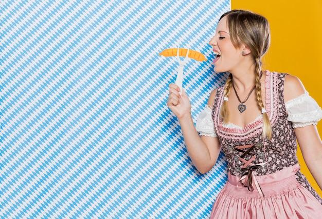 Młoda bawarska kobieta trzyma plastikowy rozwidlenie