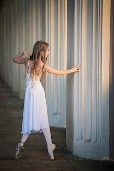 Młoda bayerina w długiej białej spódnicy z długimi luźnymi włosami stoi w wdzięcznej pozie patrząc wstecz