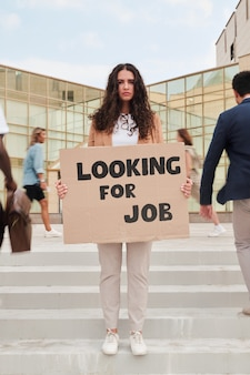 Młoda bezrobotna kobieta stojąca na schodach i trzymająca kawałek tektury z zawiadomieniem o poszukiwaniu pracy między przechodzącymi obok niej osobami